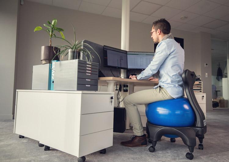 Stéphane assis sur une Tonic Chair® Originale bleu au bureau